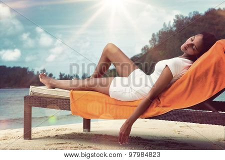 Young woman relaxing on her summer vacation lying on her back on a recliner chair on the beach with her eyes closed under the hot rays of the tropical sun