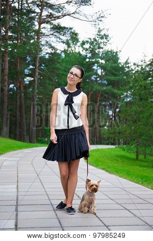 Happy Teenage Girl In School Uniform Walking With Dog Yorkshire Terrier In Park