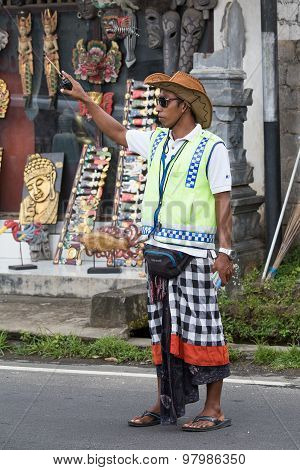 Balinese parking attendant on the main street of Ubud