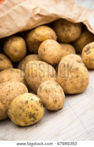 Potatoes spilling out of paper bag