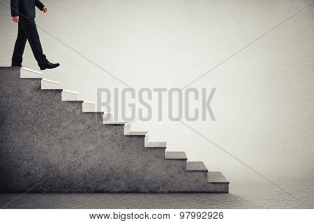 businessman in formal wear walking down the steps  over grey background