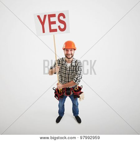 cheerful builder holding poster with word yes. isolated on white background