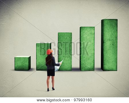 back view of businesswoman with blueprint looking up at top of concrete green diagram over grey background