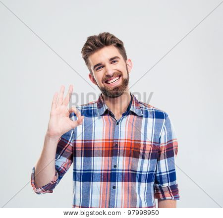 Portrait of a smiling handsome man showing ok sign with fingers isolated on a white background. Looking at camera