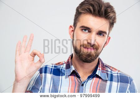 Portrait of a happy young man showing ok sign with fingers isolated on a white background. Looking at camera