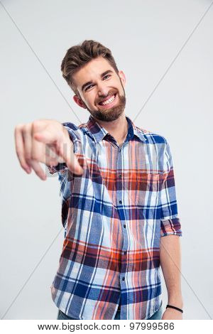 Happy young man pointing finger at camera isolated on a white background