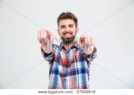 Smiling handsome man pointing fingers at camera isolated on a white background