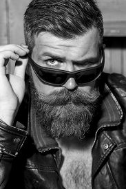 picture of long beard  - Portrait of handsome brutal unshaved man with long beard and moustache in leather biker jacket and sunglasses looking forward black and white closeup vertical picture - JPG