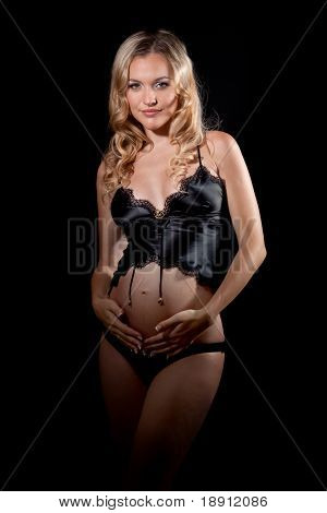 Beautiful pregnant blond woman in lingerie holding her belly. Isolated on black background