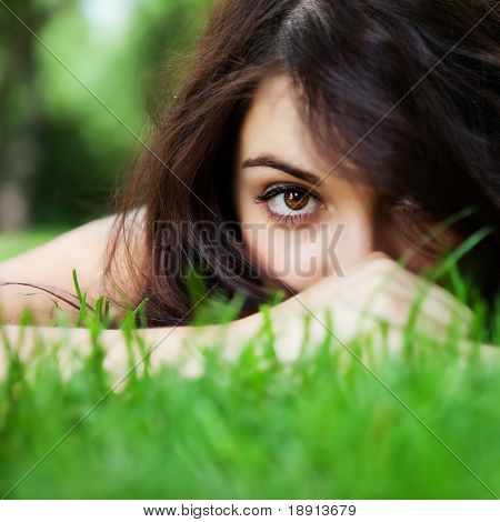 Beautiful woman in the summer park hiding in grass