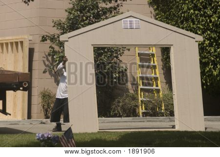 Laborers Building A Shed With Yellow Ladder