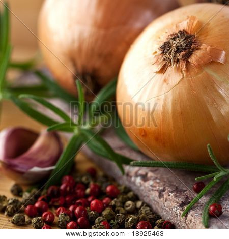 Closeup of onions, herbs and peppercorns