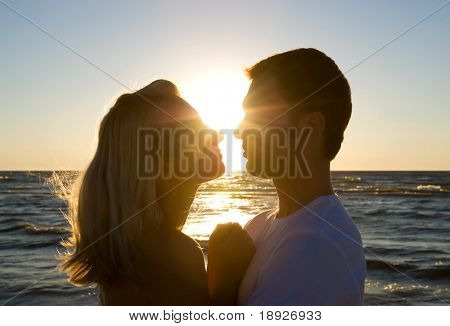 Couple hugging, enjoying summer sunset.