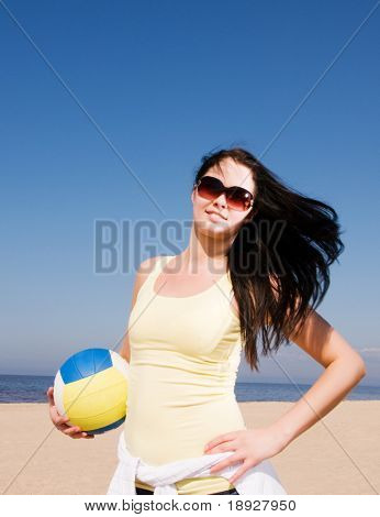 Beautiful woman playing volleyball at the beach