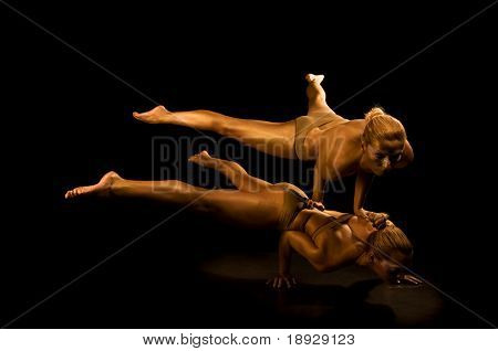 Two acrobatic girl toned in gold