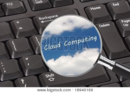 Magnifying glass showing clouds on a keyboard. Concept for cloud computing
