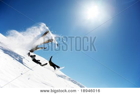 Snowboarders launching off a jump; La Thuile , Aosta, Italy.
