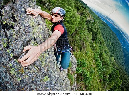 Young white man climbing a steep wall in mountain, rock-climb extreme sport, summer season. Horizontal orientation