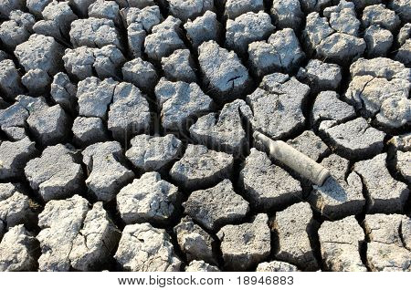 background: cracked dried ground with discarded bottle