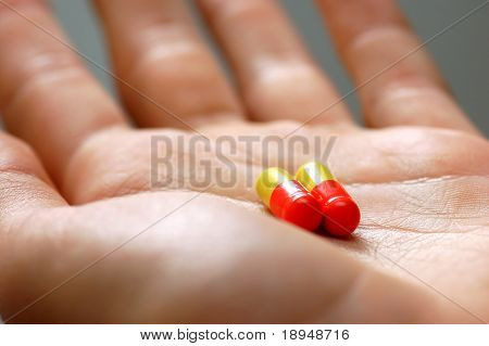 Taking pills. Hand with two capsules