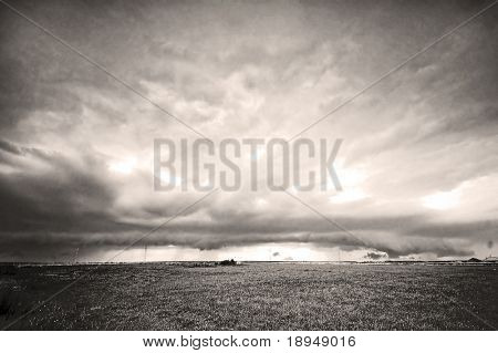 Grassland and stormy rainy sky. Ideal as a background. B&W version with added noise