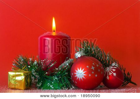 Christmas decoration with candle, balls, branches and small gift on red background