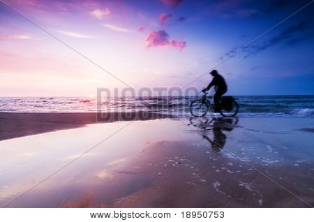Healthy lifestyle, sport. Riding a bike on the beach at sunset