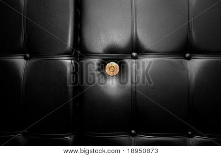 Gold peephole in luxury black leather door in retro style. Conceptual