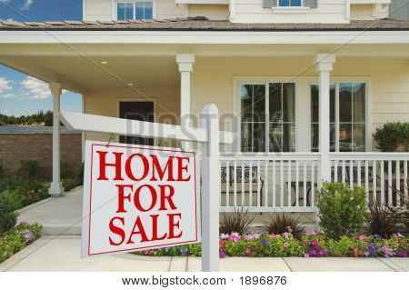 Home For Sale Sign In Front Of Beautiful Lakefront New Home