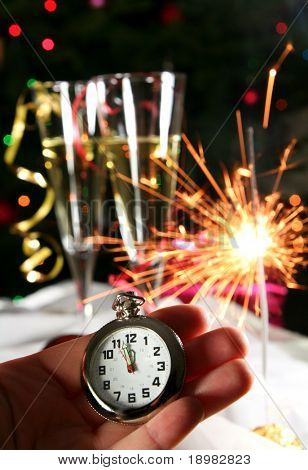 happy New Year! Old watch, sparklers champagne glasses on Christmas lights background.