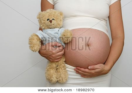 Nine month old belly and sweet teddy bear. Third trimester.