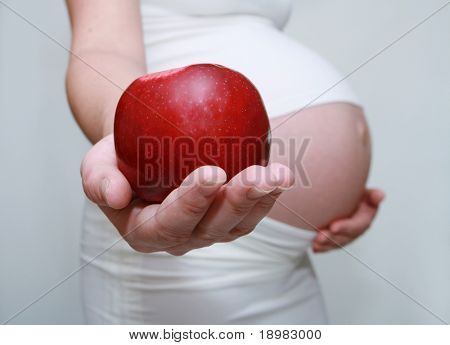 Pregnant woman holding apple. Nine month. Third trimester.