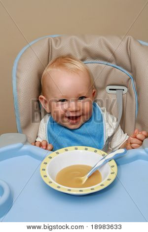 10 months old baby boy practice eating. Happy baby with a spoon.