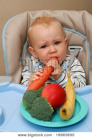 11 months old baby boy eating vegetables and fruits.