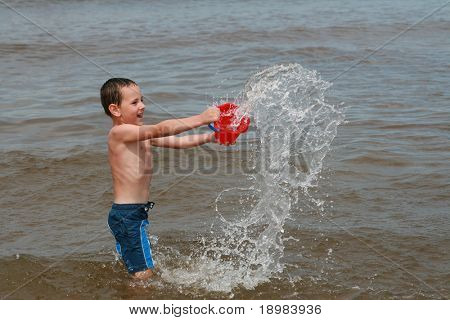 Happy summer child. Kid playing on the beach.5 years old boy splashing.
