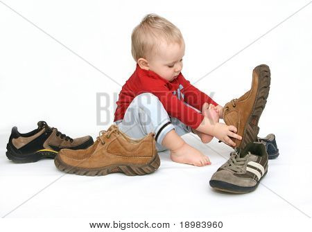 Small child tries to put on his father's shoes. Baby boy with big shoes in hand isolated on white.