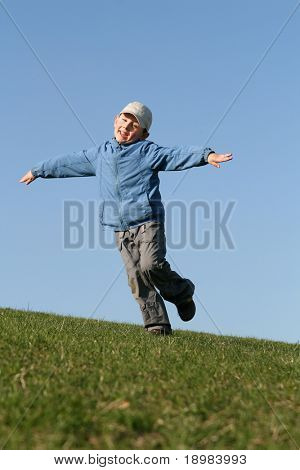 5 years old child jumping on the grass. Happy kid flying on blue sky.
