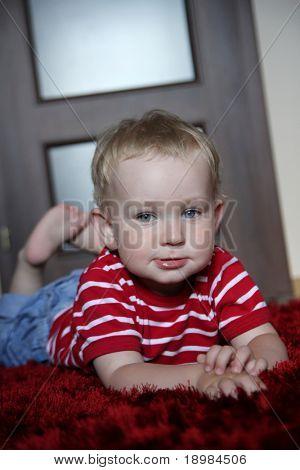 happy baby boy lying prone on a fur, red carpet in a modern room