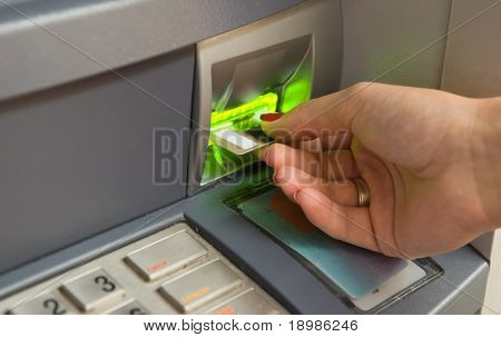 Cash withdrawal. Woman's hand inserting plastic card Visa into the ATM