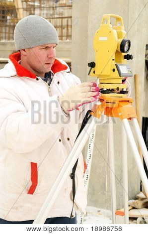 Land surveyor and equipment theodolite at a construction site in winter