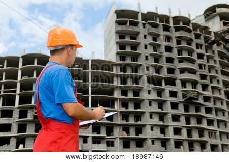 One builder worker with clipboard inspecting works at construction site