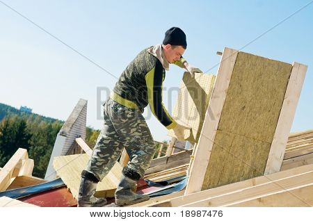 builder roofer working with insulation material at construction works