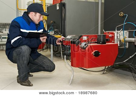 maintenance engineer tuning heating system equipment in a boiler room
