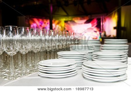 Empty clean commercial white plates and stemware glass before party time