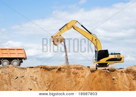 Loader Excavator loading body of a dump truck tipper at open cast over blue sky in summer