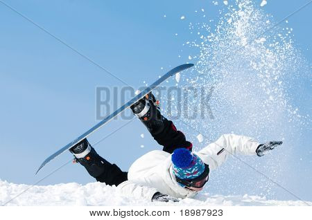 falling young man on snowboard at snowy winter