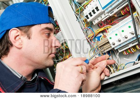 One electrician working on a industrial panel mounting and assembling new wiring