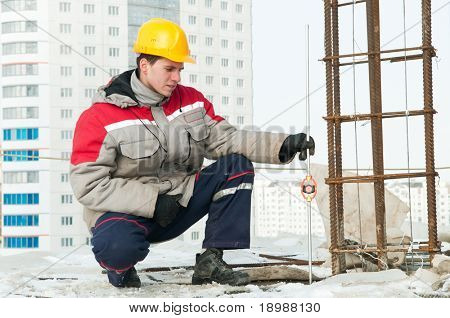 Surveyor worker assistant working at construction site in winter with survey target