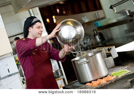 professional chef adding water into big pot for vegetable boiling in kitchen