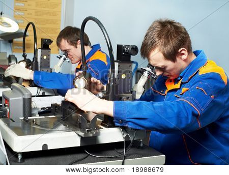 two workers technicians checking detail quality in tool workshop